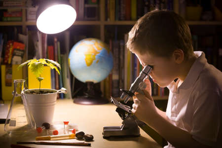 Close-up portrait of young student working with microscope in his room. Child and science experiments. Kid studying samples under the microscope. Preparing for science lesson.