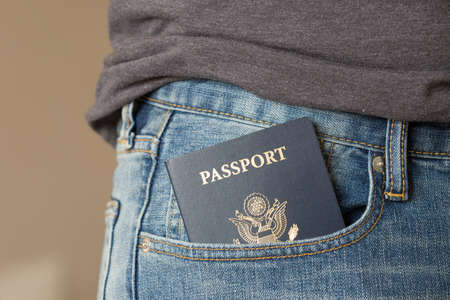 Closeup of US passport in themans  jeans pocket. Ready for traveling and vacations.