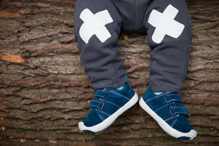 babys: Close-up of babys legs in sneakers on the wooden tree background. Little child sitting on old tree - image of legs and feet.
