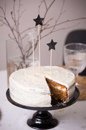 tiffany blue: Close up of delicious homemade birthday white cake decorated with silver stars on the table. Baking at home for events. Cooking sweet cake for holidays. indoors.Carrot cake with white icing.