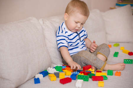 striped shirt: Cute little toddler boy in a striped shirt playing with colorful plastic blocks on the sofa indoors. child having fun and building out of bright constructor bricks. Early learning. Creative.