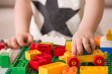 테이블에 다채로운 플라스틱 벽돌을 가지고 노는 아이의 손을 닫습니다. 유아 재미와 밝은 생성자 벽돌에서 건물입니다. 초기 학습. 스트라이프 배경.  스톡 콘텐츠