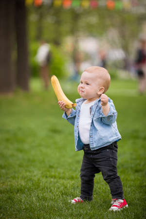 first day: Cute little toddler boy with banana walking in the park on a summer day. First babys steps. Outdoor. Child taking first steps on the green grass.