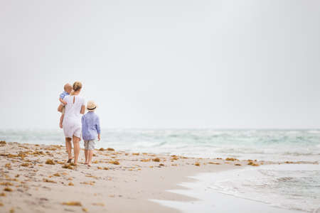 그녀의 두 어린 소년 바다 해변을 따라 걷고 흰 드레스에 젊은 어머니. 아기와 바다로 휴가를 즐기는 소년 여자. 빈 해변에서. 어머니.