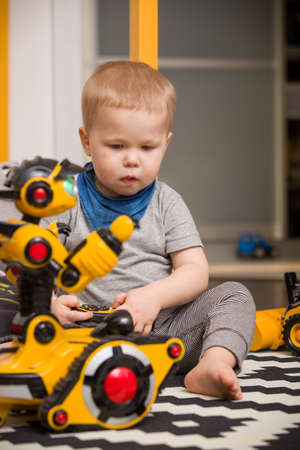 toddler boy: Little toddler boy playing with funny robot toy at home, indoors. Innovation technology concept. Children and technology. Stock Photo
