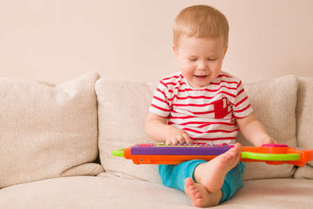 young musician: Portrait of adorable toddler boy sitting on the sofa and playing toy piano. Early learning at home. Little musician. Child and toys.Education. Indoors.
