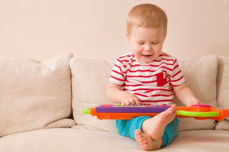 musico: Retrato de niño adorable niño que se sienta en el sofá y tocar el piano de juguete. El aprendizaje temprano en casa. Poco músico. Infantil y toys.Education. Adentro. Foto de archivo