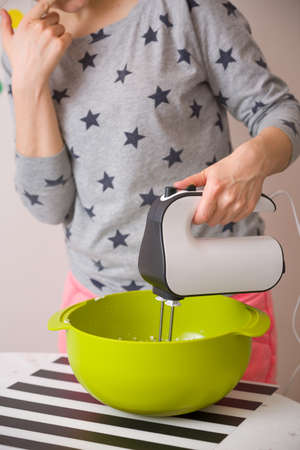 long sleeve shirt: Young woman in long sleeve shirt with stars mixing and tasting dough for homemade muffins. Cooking and baking at home. Bright kitchenware and white mixer. Indoors.