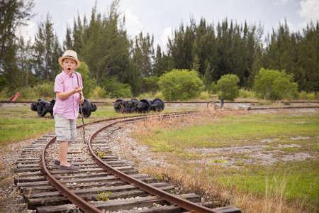 return trip: Cute kid boy in straw hat goes on rails,in field, in the summer. Child walking along old railroad.