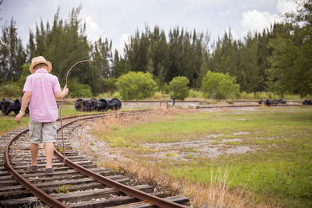 return trip: Cute kid boy in straw hat goes on rails, back to a camera, in field, in the summer. Child walking along old railroad. Stock Photo