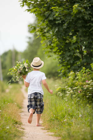 bare feet: Back view on cute bare feet kid boy in straw hat running on a countryside road and holding bunch of wild flowers. Child running in the park. Outdoors. Happy summer and lifestyle concept. Childhood.