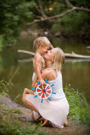 day dreams: Young mother and boy seaman with sailing wheel by the river on a warm summer day. Dreams of travel! Woman hugging child against the backdrop of nature. Future captain. Happy family outdoors.