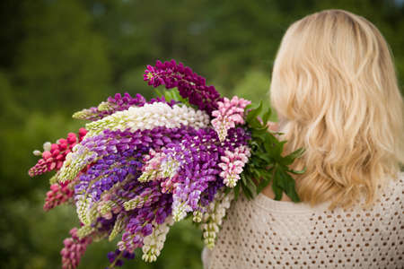 lupin: Back view on young girl holding a bunch of beautiful lupine flowers. Purple and pink lupin bouquet. Womanl with bouquet of wild  lupin flowers on sunny summer field.