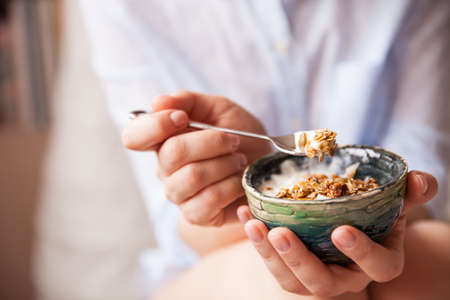 cereals holding hands: Young woman with muesli bowl. Girl eating breakfast cereals with nuts, pumpkin seeds, oats and yogurt in bowl. Girl holding homemade granola. Healthy snack or breakfst in the morning..