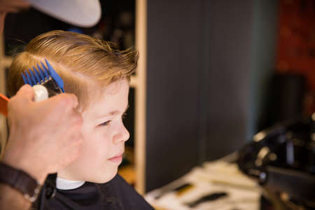 Close-up of man hands grooming kid boy hair in barber shop. Boy cut with hairdresser's machine. Portrait of male child at the barber shop to cut his hair.