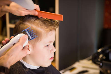 Close-up of man hands grooming kid boy hair in barber shop. Boy cut with hairdressers machine. Portrait of male child at the barber shop to cut his hair.