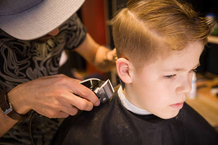 male grooming: Close-up of man hands grooming kid boy hair in barber shop. Boy cut with hairdressers machine. Portrait of male child at the barber shop to cut his hair.