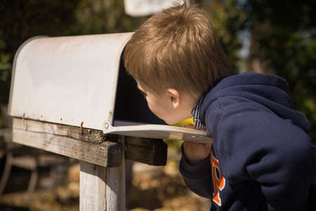 School boy opening a post box and checking mail. Kid waiting for a letter, checking correspondence and looking into the in the metal mailbox. 写真素材