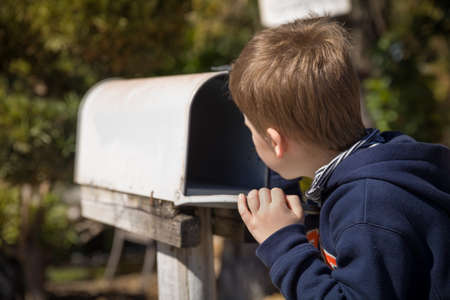 School boy opening a post box and checking mail. Kid waiting for a letter, checking correspondence and looking into the in the metal mailbox. Banque d'images