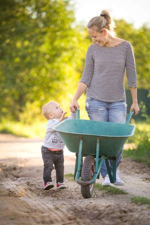 niño empujando: Adorable niño chico y su madre que recorre a lo largo de la carretera nacional y empuja la carretilla en un día soleado. Verano trabaja en el jardín. Niño ayudar a mamá. Foto de archivo