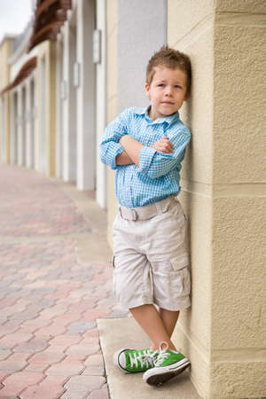 boy shorts: Kids fashion concept. casual child stands with his back against street wall.Outdoor portrait of a cute little blond boy wearing shorts and shirt standing next to stone wall