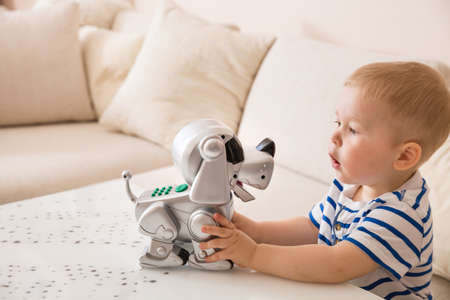 Adorable toddler boy playing with interactive toy. Child with toy robot dog. indoors. Activities for small children. Communication and digital concept. Reklamní fotografie - 58411687
