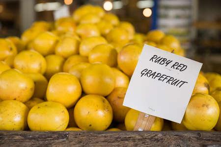 florida citrus: Pile of orange ruby grapefruit on the wooden table in the market. Fruit harvest. Local farm market. Healthy fruit. Vitamins.