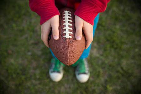 맑은 날에 경기장에 축구를 들고 작은 아이 소년의 손에 상위 뷰. 축구를 던질 준비가 된 아이. 스포츠 개념입니다. 야외 활동을하는 아이들을위한 스 스톡 콘텐츠