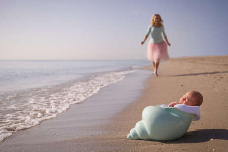 nutshell: Beautiful woman running to her newborn baby boy on the sandy ocean beach. Happy mother meeting her child. Newborn baby in the nutshell on the sea shore on sunny day. Motherhood and childhood concept.