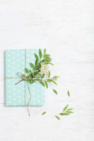 정원의 나뭇 가지와 꽃 장식 생일 선물 스택. 파티에 선물 포장. 꽃 장식과 청록색 종이 선물 포장. 휴일 개념입니다. 플랫 누워. 스톡 콘텐츠