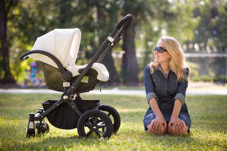 Young woman with her newborn baby enjoying sunny summer day in the park. Mother with child in the stroller outdoors. Motherhood.  Mum with baby walking in the city. Stock Photo