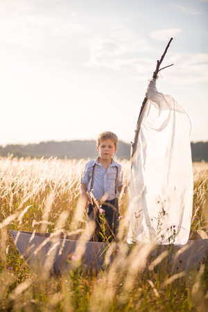 seaman: Boy seaman floats on a sailing boat in the field at sunset on a warm evening summer. Dreams of travel! Child floats on a handmade boat against the backdrop of a sunset.