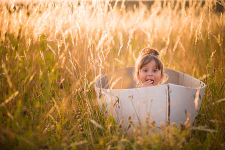 seaman: Adorable kid girl seaman floats on a sailing boat in the field at sunset on a warm evening summer. Dreams of travel! Child floats on a handmade boat against the backdrop of a sunset.