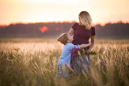 Mignon enfant garçon étreindre sa mère sur une prairie d'été sur beau coucher de soleil d'été. Happy family ensemble. Maman et enfant. La maternité et l'enfance. la marche de la famille dans le domaine. En plein air. Banque d'images