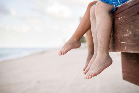 ragazze a piedi nudi: I piccoli bambini seduti sul molo di legno in acqua e godendo giorno d'estate. I piedi nudi di ragazzo e una ragazza. Vacanza al mare. All'aperto. Fratelli. Sorella e fratello in riva all'oceano.