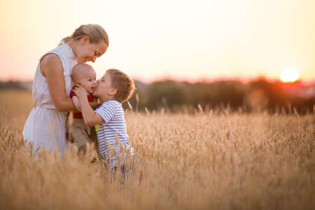 little blonde girl: Happy family enjoying sunset in wheat field. Beautiful young woman with adorable baby boy and kid boy. Mother hugging her two children on a meadow on a sunny evening. Mom and sons. Outdoors.