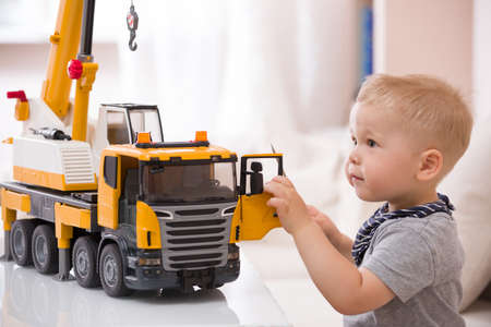 educative: Portrait of adorable smiling toddler boy sitting at the table playing with a big construction car at home. Little child with toy car. Educative toys for children. Early learning and developing concept