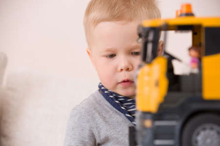 educative: Portrait of adorable toddler boy sitting at the table playing with a big construction car at home.Little child with his toy car. Educative toys for children. Early learning and developing concept.