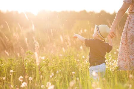 그의 어머니의 손을 잡고 거리를 가리키는 밀 짚 모자에 귀여운 작은 유아 소년에보기를 다시. 화창한 여름 날에 그의 엄마와 함께 공원에서 산책하는
