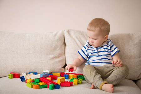 baby playing: Cute little toddler boy in a striped shirt playing colorful plastic blocks on the sofa indoors. child having fun and building out of bright constructor bricks. Early learning. Creative. Stock Photo