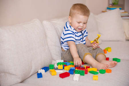 early childhood: Cute little toddler boy in a striped shirt playing colorful plastic blocks on the sofa indoors. child having fun and building out of bright constructor bricks. Early learning. Creative. Stock Photo
