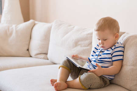 Adorable blond toddler boy laying on the sofa and playing with tablet pc at home, indoors. Child with tablet computer. Stock Photo