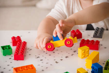 early childhood: Close up of childs hands playing with colorful plastic bricks at the table. Toddler having fun and building out of bright constructor bricks. Early learning.  stripe background. Developing toys
