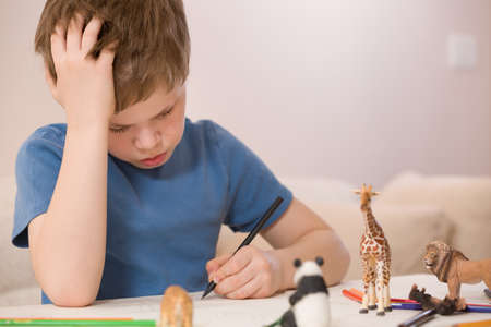 school activities: Portrait of little school boy sitting at the table and drawing with color paint. After school activities at home. Education. Small boy creating handmade cards. Stock Photo