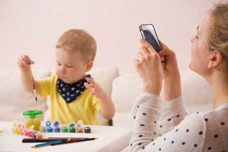 Young mother taking photo of cute little toddler boy in yellow shirt sitting at table and drawing with colorful paints. Early learning. Creative. Toddler drawing. Mom making picture on mobile phone Stock Photo