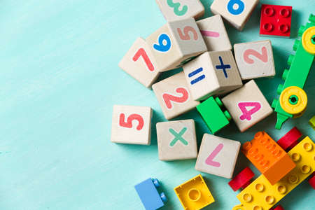 child learning: Wooden cubes with numbers and colorful toy bricks on a turquoise wooden background.