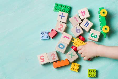 자식 나무 큐브 숫자와 화려한 장난감 벽돌 청록색 목조 배경에 놀기. 유아 학습 번호입니다. 장난감을 가지고 아이의 손입니다. 스톡 콘텐츠