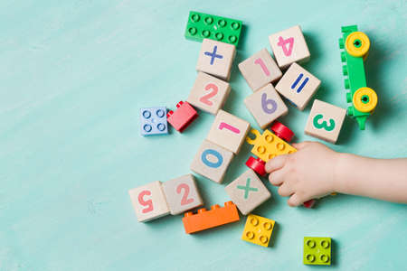 baby blocks: Child playing with wooden cubes with numbers and colorful toy bricks on a turquoise wooden background. Toddler learning numbers. Hand of a child taking toys.