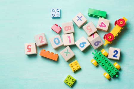 Wooden cubes with numbers and colorful toy bricks on a turquoise wooden background.