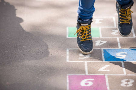 Closeup of boy's legs and hopscotch drawn on asphalt. Child playing hopscotch on playground outdoors on a sunny day. outdoor activities for children. Stock Photo